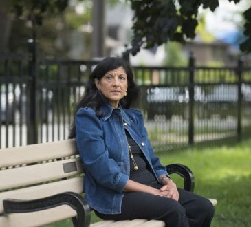 Zabeen Hirji sits on bench in Toronto park.