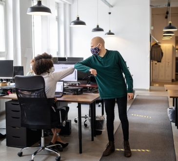 Man and woman touching elbows in office.
