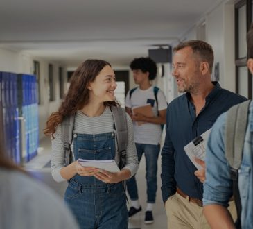 Female high school student and male teacher walking in hallway talking amid other students.