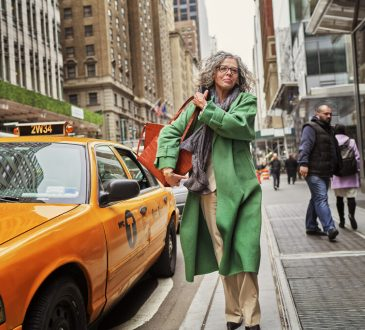 Older professional woman exits cab in NYC.