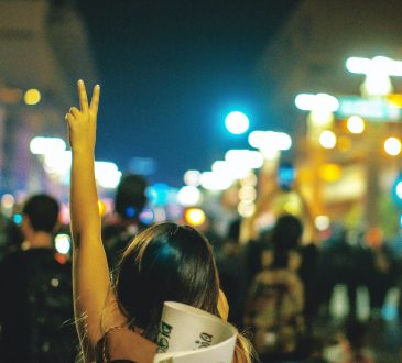 Woman holding up hand in peace sign in midst of protest march.