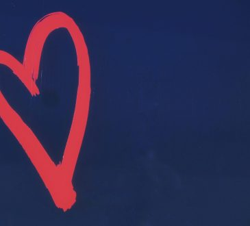 Red heart painted on blue wall.
