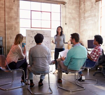 Group of people watching woman present in office