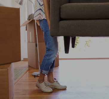 Close up of woman carrying sofa moving into home.