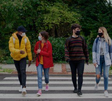 Four college students walking across crosswalk wearing masks.