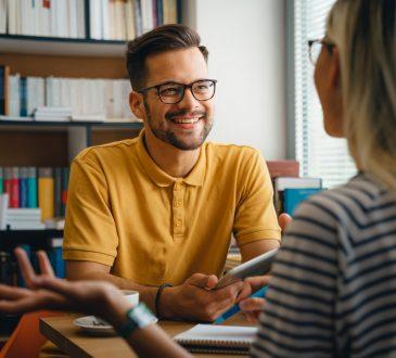 Female student talking to male university advisor in office.