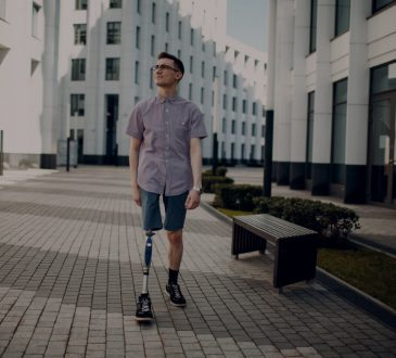 Man with right leg prosthesis walking on sidewalk in city.