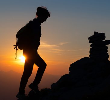 Silhouette of woman hiking up mountain against sunset.