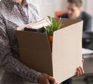 Closeup of woman holding cardbox box with office belongings.