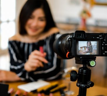 Woman sitting at table recording video of self with camera on tripod.