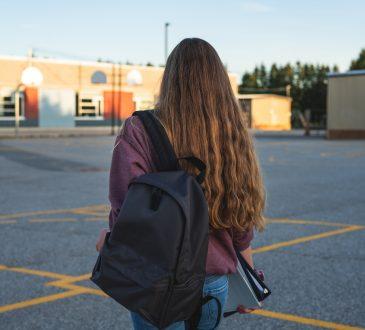 Teen girl walking through school's outdoor basketball court.