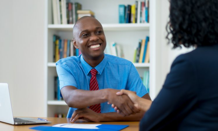 Man in bright blue button-up shirt shaking hands with woman in job interview
