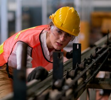 Woman working on machinery in factory.