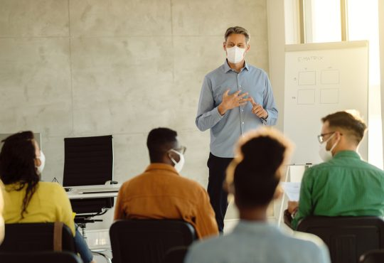 University professor wearing protective face mask while holding a class to group of students during coronavirus epidemic.
