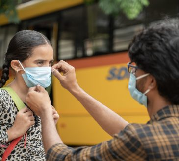 Father helping daughter to wear mask before getting inside the school bus.