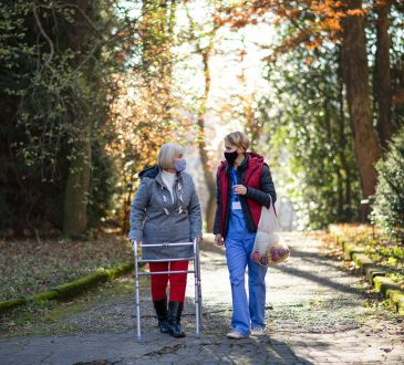 Senior woman using walker and female healthcare working walking outdoors on path in fall