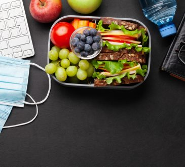 Healthy office lunch box with sandwich and fresh vegetables, water bottle, nuts and fruits on desk.