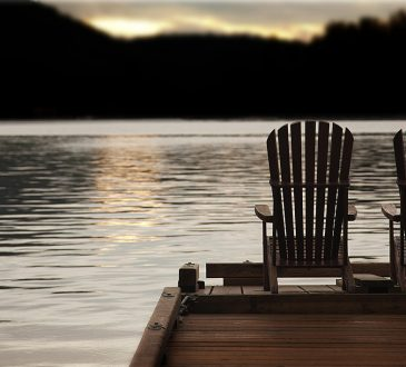 Adirondack chairs on a pier at sunset by the lake or ocean.