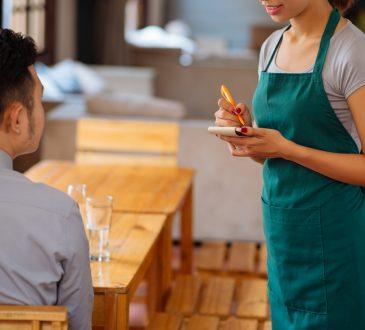 Waitress taking order from customer in restaurant.