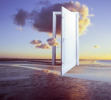 Photo illustration of door on beach opening into clouds