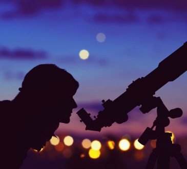 Silhouetted woman looking through telescope
