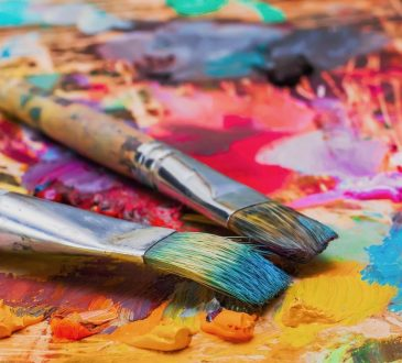 Used brushes on an artist's palette of colourful oil paint.