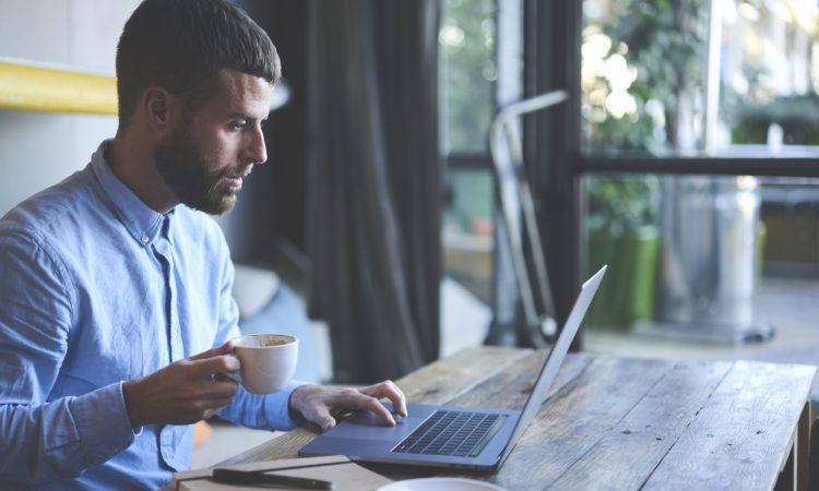 Man watching webinar on laptop.