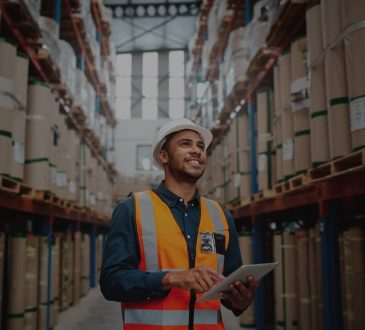 Young man wearing safety jacket in warehouse holding clipboard.