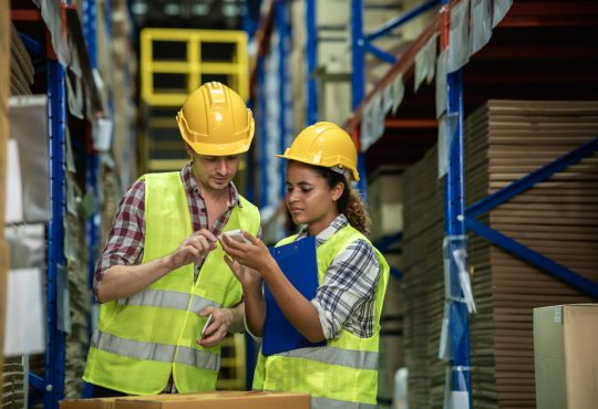 Man and woman discussing inventory in warehouse.