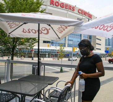Female server wiping tables outside Rogers Centre in Toronto.