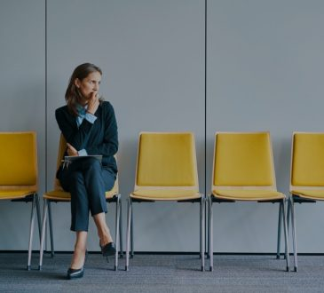 Woman sitting in yellow chair in interview waiting room.