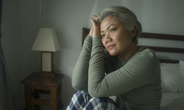 Middle-aged woman sitting in bed wearing pyjamas and looking worried