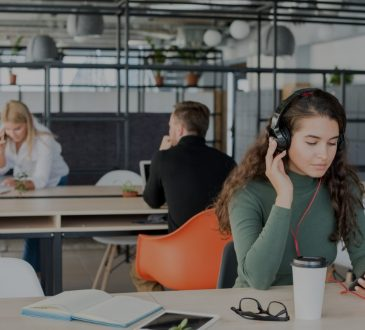 Young woman wearing headphones in open-concept office.