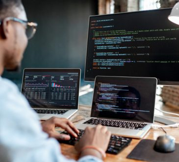 Man coding on laptop and computer.