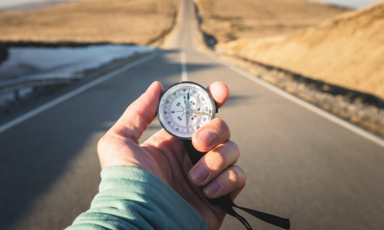 Compass in hand in front of mountain road background.