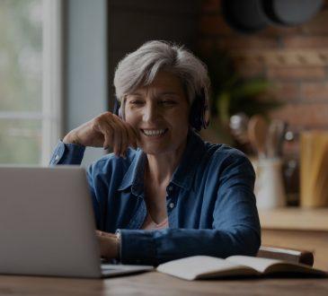 Older woman watching something on laptop screen at home.