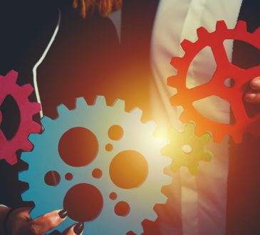 Teamwork of businesspeople work together and combine pieces of gears.