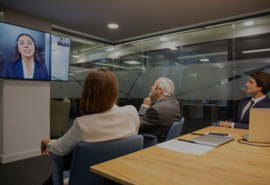 People sitting in boardroom having conversation with woman on teleconferencing on tv screen.