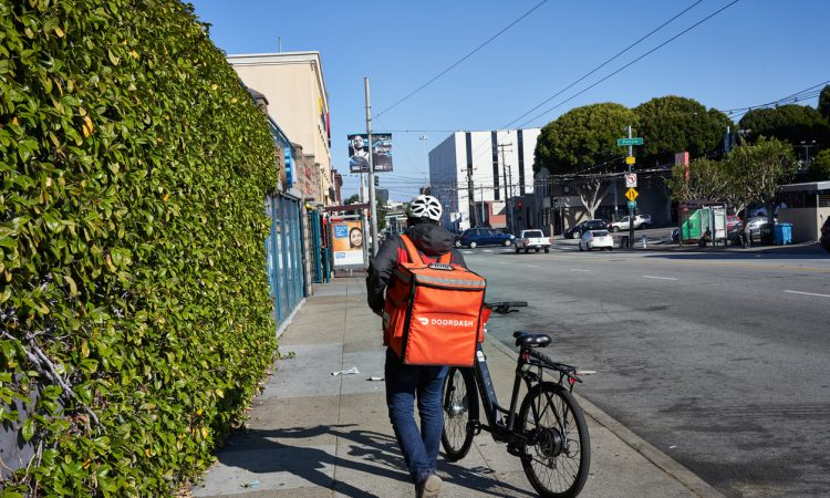A DoorDash delivery worker walks his bike along the road.