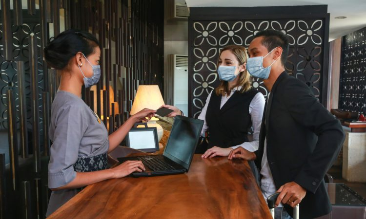 Couple and receptionist at counter in hotel.