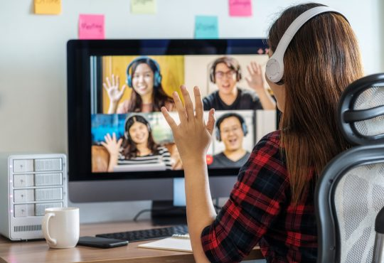 Woman joining video call with colleagues.