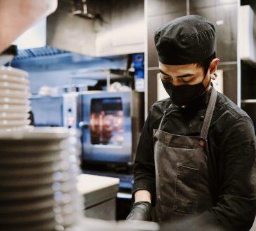 Chef wearing mask while working in restaurant kitchen.