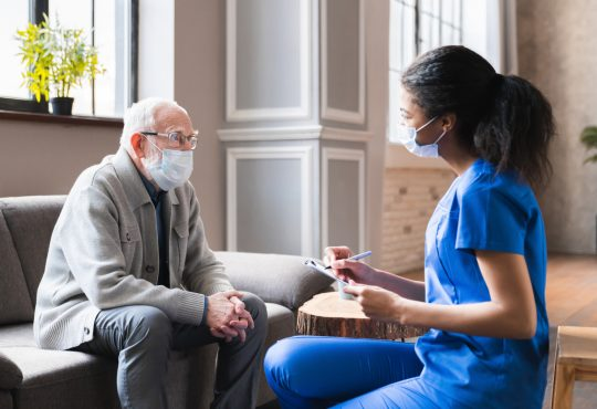 Young woman health aide consulting with older male patient during home visit.