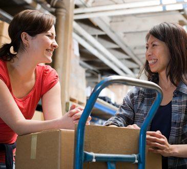 Two women talking in warehouse.