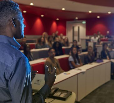 Man lecturing students in a university lecture theatre.