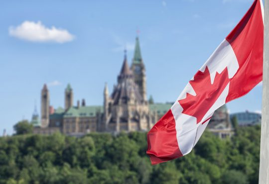 Canadian flag waving with Parliament Hill in the background.