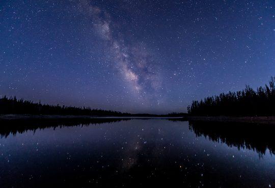 Stars in night sky reflecting on lake.
