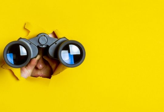 Person using binoculars to look through hole torn in large sheet of yellow paper.