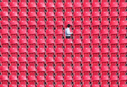 One person walking among empty red stadium seats.