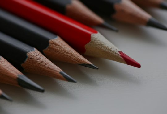 Red pencil in line of black pencils on white sheet.